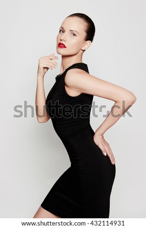fashion portrait of glamor beautiful young woman in a black dress posing in the studio,luxury.beauty sexy girl with red lips - stock photo