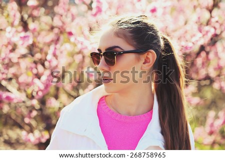 Fashion portrait of gorgeous young sexy blond girl posing in a lush garden in the spring in a stylish white jacket, a pink blouse and striped skirt and sunglasses. Bright young outfit. Image toned - stock photo