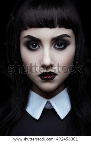 Fashion portrait of gothic young girl on black