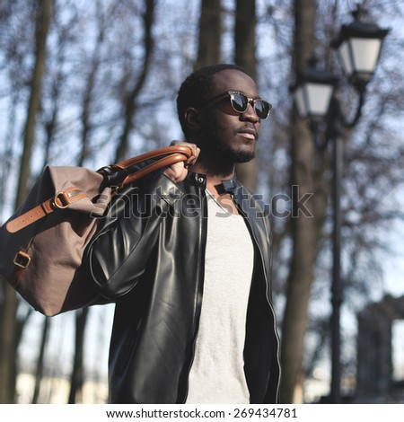 Fashion portrait of handsome african man in black leather jacket with bag outdoors - stock photo