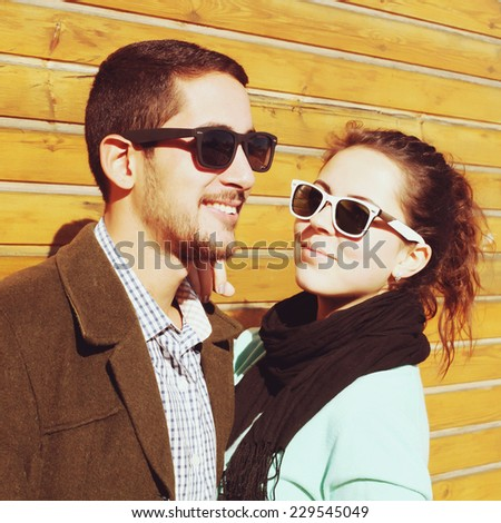 Fashion portrait of happy smiling young vintage hipster pretty couple having fun outdoor on the street. Modern urban people, wooden background. Photo toned style Instagram filters. - stock photo