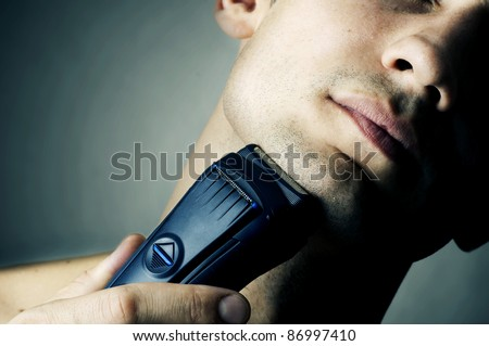 Fashion portrait of male chin and electric shaver - stock photo