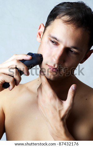 Fashion portrait of man shaving chin and cheek by electric shaver. Male hygiene - stock photo