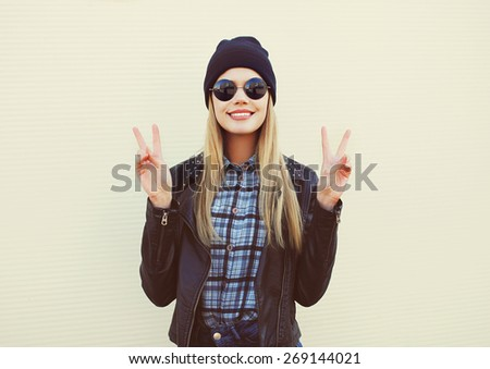 Fashion portrait of pretty blonde girl in trendy rock style posing and having fun outdoors  - stock photo