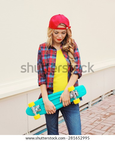 Fashion portrait of pretty cool girl in red cap, checkered hipster shirt with skateboard outdoors - stock photo