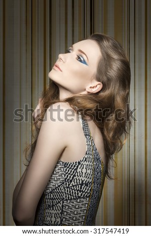 fashion portrait of pretty girl with long wavy hair, blue stylish make-up and vintage printed dress  - stock photo