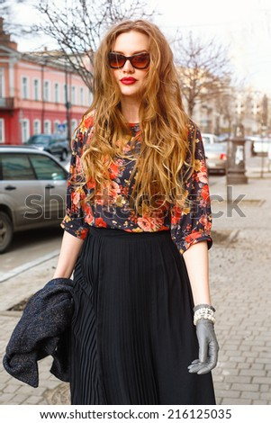 Fashion portrait of pretty stylish young woman walking alone at the street at old european city town, and have fun, wearing retro elegant clothes and sunglasses. Vintage autumn style. - stock photo