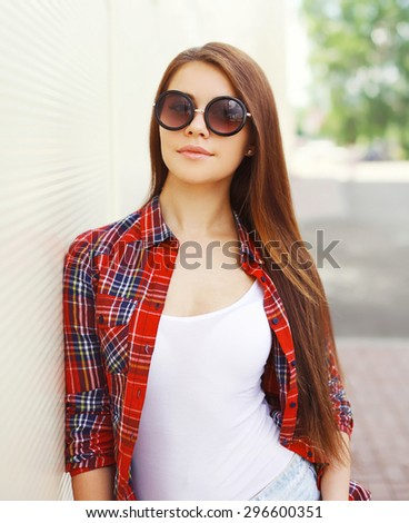 Fashion portrait of pretty woman in the sunglasses and checkered shirt outdoors - stock photo