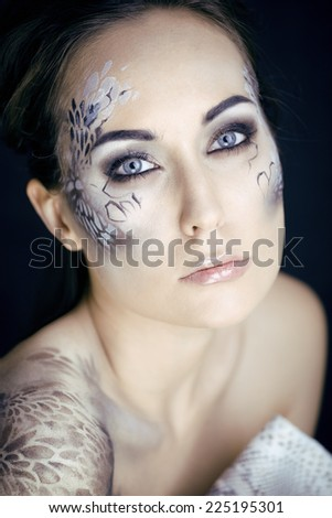 fashion portrait of pretty young woman with creative make up like a snake,  victim with python skin clutch, halloween - stock photo