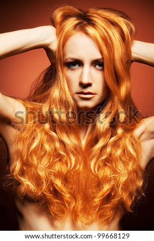 Fashion portrait of redhead woman with long hair on brown background