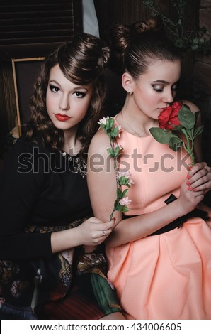 Fashion portrait of romantic beautiful couple of pretty girl with hairstyle, make up, vintage dress. Girls holding, smelling rose flower. Fashionable sexy pair of young women in fantasy stylization.