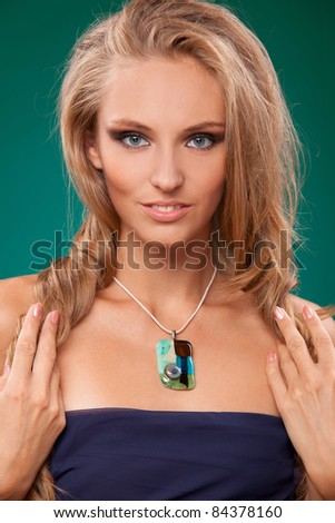 Fashion portrait of sensual blond female showing her beautiful necklace - stock photo