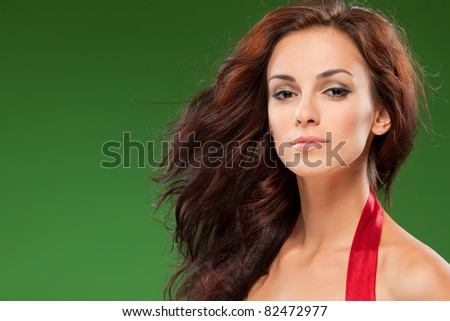 Fashion portrait of sensual female with hair lightly fluttering in the wind over green background - stock photo
