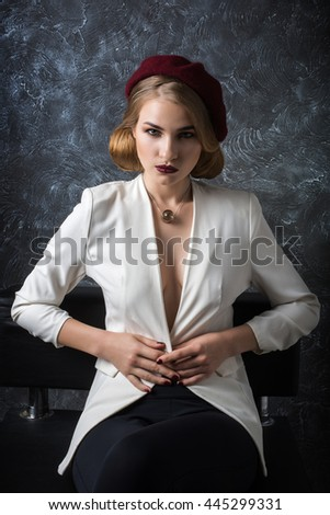 Fashion portrait of sexual blond woman with provocative glossy red and business clothes over grey background.