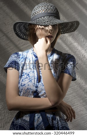 fashion portrait of sexy brunette girl with blue printed clothes and black hat, with charming expression  - stock photo
