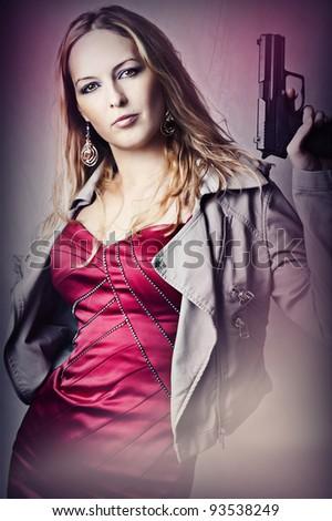Fashion portrait of sexy dangerous woman holding gun - stock photo