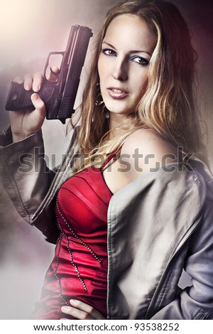 Fashion portrait of sexy dangerous woman holding gun - stock photo
