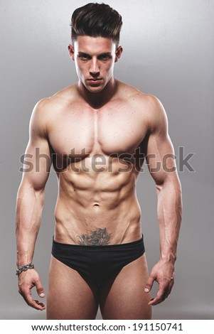 Fashion portrait of sexy male fitness model against grey background not isolated.Fashion colors.