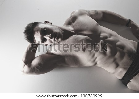 Fashion portrait of sexy male fitness model against neutral background
