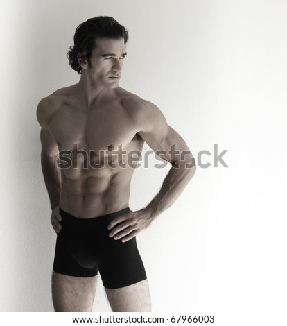 Fashion portrait of sexy male fitness model against neutral background - stock photo
