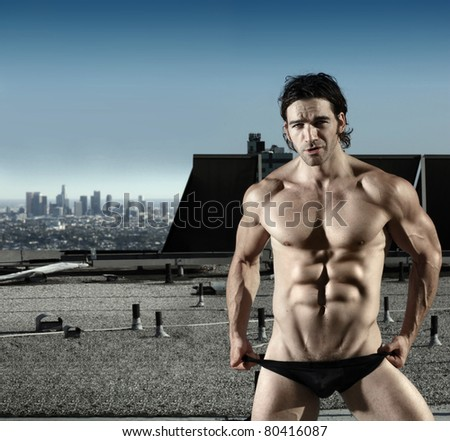 Fashion portrait of sexy male model in black briefs on top of roof with city in background - stock photo