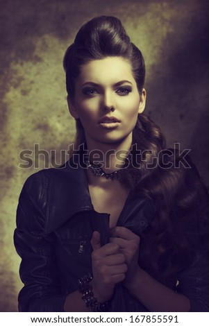 fashion portrait of sexy modern woman with long brown wavy creative hair-style, dark rock style wearing leather jacket