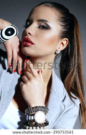 Fashion portrait of sexy young brunette girl with evening makeup wearing beautiful jewelry and posing at studio