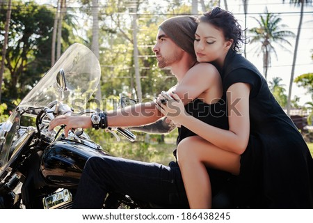 Fashion portrait of stunning couple riding bike in tropical country wearing stylish monochrome black clothes. - stock photo