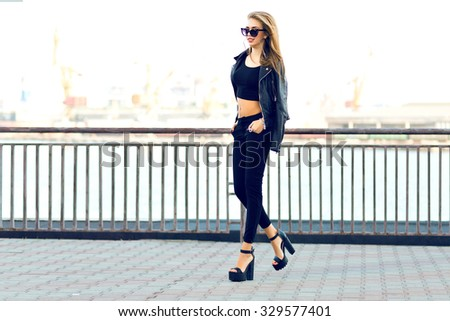 Fashion portrait of stunning sexy blonde woman, wearing brutal total black outfit, sunglasses, leather jacket, long hairs, vintage toned film colors, windy cold weather, autumn time, urban style. - stock photo