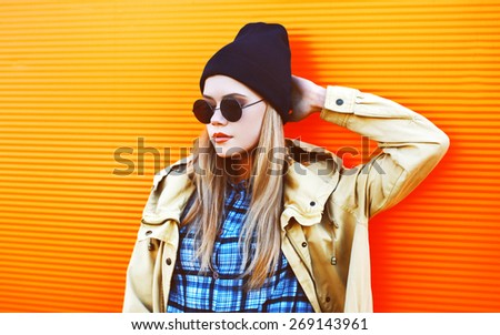 Fashion portrait of stylish hipster girl posing outdoors in the city against a colorful wall - stock photo