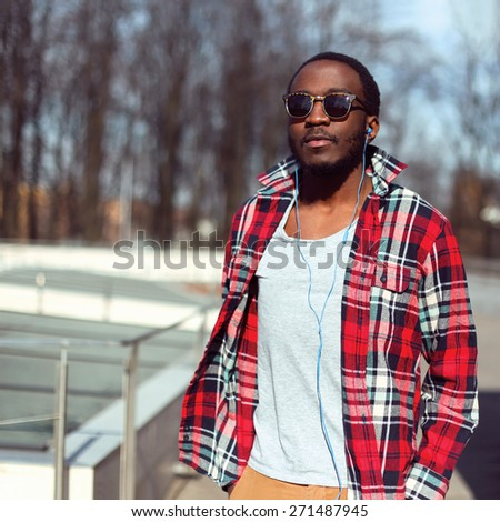 Fashion portrait of stylish young african man listens to music in earphones outdoors, handsome hipster wearing a plaid red shirt and sunglasses  - stock photo