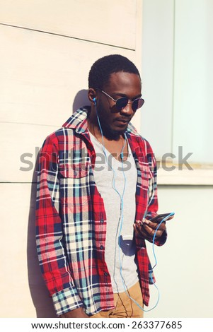 Fashion portrait of stylish young african man listens to music on the smartphone, hipster wearing a plaid red shirt and sunglasses against the urban wall outdoors - stock photo