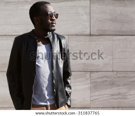 Fashion portrait of stylish young african man wearing a sunglasses and black rock leather jacket over textured background - stock photo