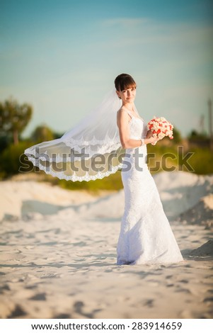 Fashion portrait of tender stylish bride with simple modern wedding dress posing with amazing exotic white lotus bouquet at the beach. Evening golden sunlight - stock photo