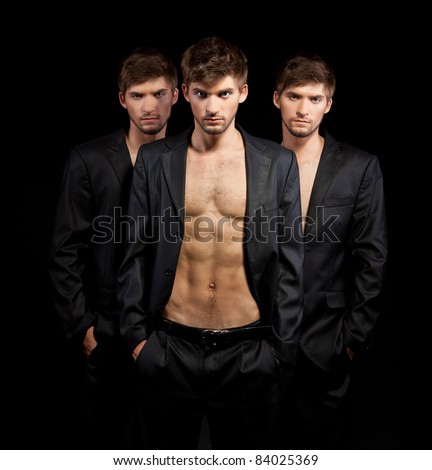 Fashion portrait of the three young beautiful brother twins men model over gray background