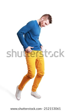 Fashion portrait of the young beautiful bearded man in studio, yellow jeans and blue top - stock photo