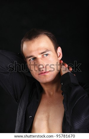 Fashion portrait of the young beautiful man, isolated on black background - stock photo