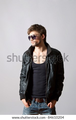 Fashion portrait of the young beautiful man posing in sun glasses over gray background
