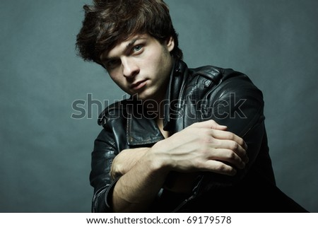 Fashion portrait of the young sexual man in studio - stock photo
