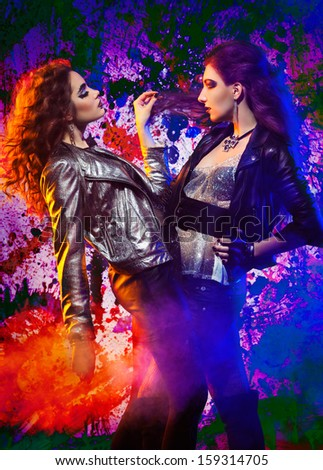 Fashion portrait of two glam rock girls posing on colorful background;  slightly inverted - stock photo