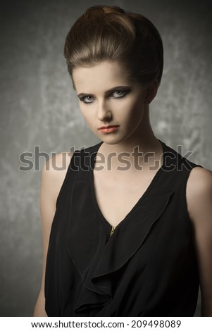 fashion portrait of very pretty young girl with creative elegant hair-style, cute make-up and stylish black dress  - stock photo