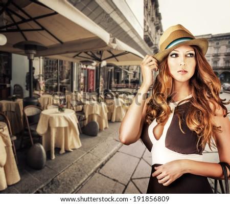 Fashion portrait of woman wearing hat walking on city street - stock photo