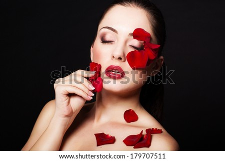 Fashion portrait of woman with red rose petals - stock photo