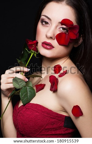 Fashion portrait of woman with rose petals and red rose flower - stock photo