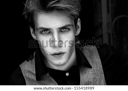 fashion portrait of young adorable man against black background