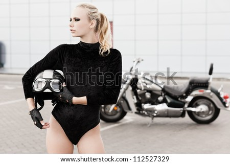 Fashion portrait of young attractive blond girl and motorcycle. Copy space on right - stock photo