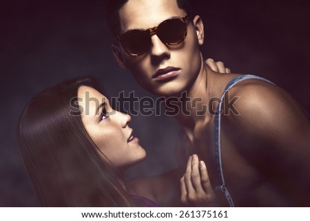 Fashion portrait of young beautiful couple against blue background - stock photo