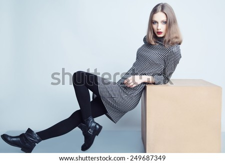 Fashion portrait of young beautiful female model with perfect make up in casual dress and boots. - stock photo