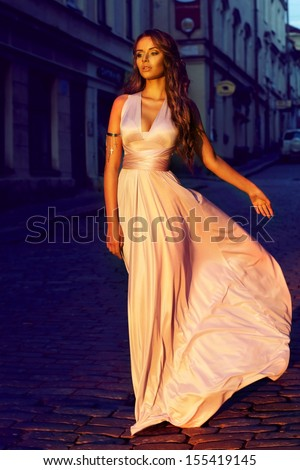 fashion portrait of young beautiful girl in pale lilac color long flying dress walking down the street in old town at sunset       - stock photo