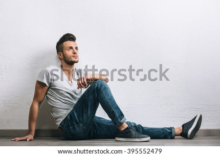 Fashion portrait of young beautiful handsome man. Added retro filter and grain/noise. - stock photo